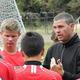 Coach Chris Burns prepares his team with a pre-game talk.