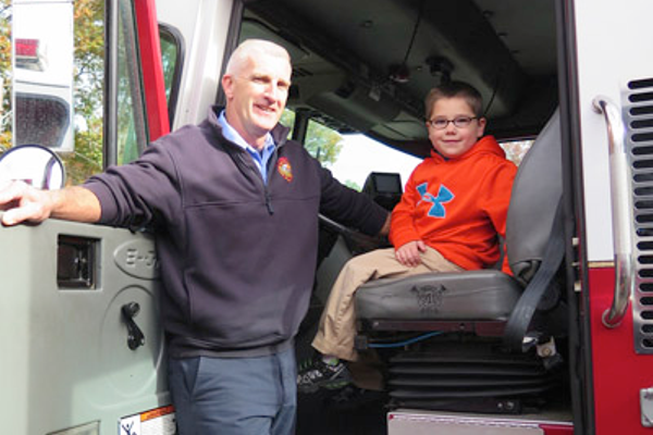 Domenic Taylor of Bellingham, age 5, gets to sit in the fire truck, with assistance from Lt. Coakley.