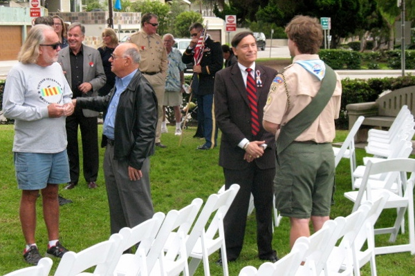 Manhattan Beach resident Bob Holmes (in shorts) talks with a community member while Mayor Wayne Powell converses with a scout after the ceremony. MB City Council member Mark Burton can be seen behind Holmes.