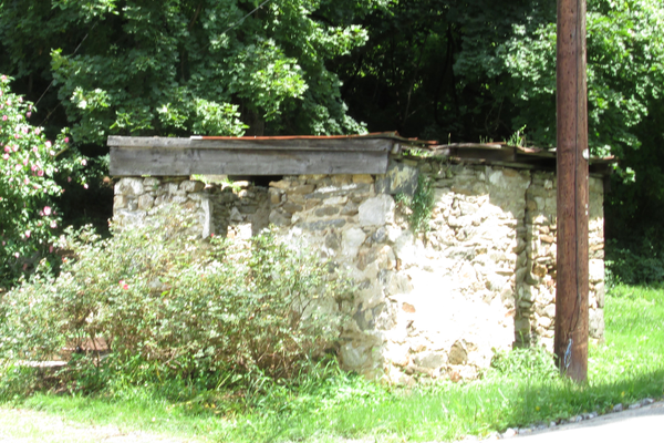This outbuilding is seen just behind the buggy in the postcard view.