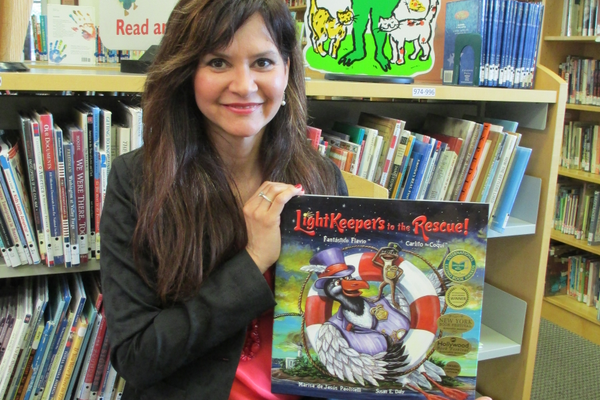 Marisa de Jesus Paolicelli in the Avon Grove Library's children's section, with a copy of her latest book, 'Lightkeepers to the Rescue!'