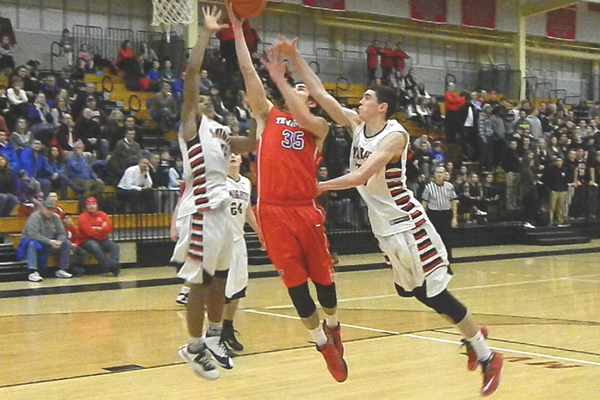 Joe Csokmay (35) drives past two North Andover defenders for two points.