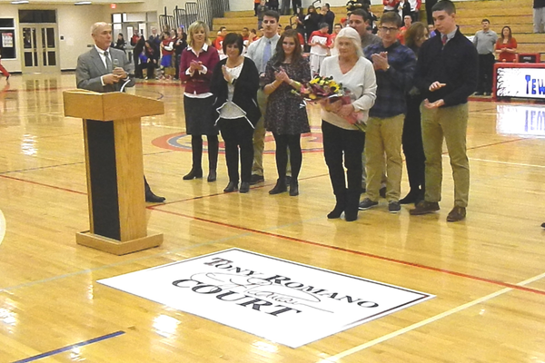 "Supertindent of Schools Dr. John O'Connor unveils the ""Tony Romano Court"" logo while the Romano family looks on."