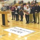 """Supertindent of Schools Dr. John O'Connor unveils the """"Tony Romano Court"""" logo while the Romano family looks on."""