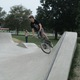 A cyclist tries out the skate spot.