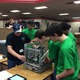 Robot undergoing inspection before a match. It must fit within 18x18x18 inches, and our robot is very close! 	L-R. Vex Robot Inspector, Brad Stalder, Zachary Kearney, Nikhil Ravi, Cameron Allen. Photo courtesy of Linda Woessner.