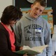 Tewksbury High athlete Scott Pastorello looks over a photo book with Mrs. Yore, his former 2nd grade teacher at the Dewing School. Scott was one of the guest readers during literacy day at the school.