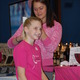 Celeste Abrams, owner of Exposed Organics, helps Pancott Gymnast Nicole Piper get ready for the Pink Invitational.
