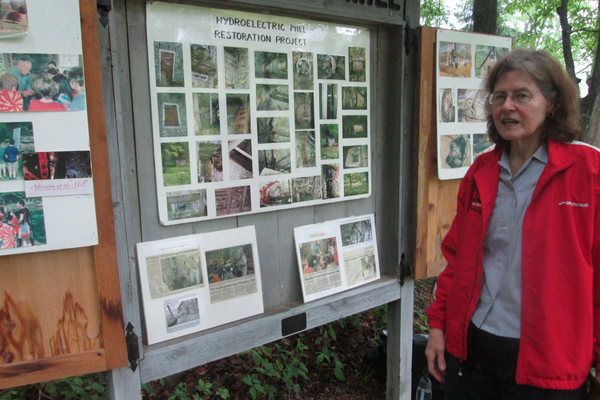 Karen Wood, with a display of photos of the mill.