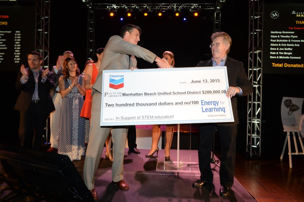 MBUSD Superintendent Mike Matthews accepts a check from Chevron.Photo credit: Axel Koester for MBEF