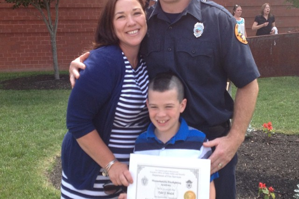 Firefighter Tyler Welch poses with his wife Jennie, and their son at Tyler's graduation ceremony from the Firefighting Academy.