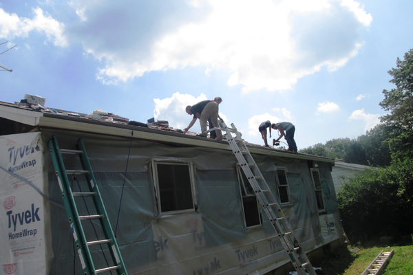 On the roof of the Craft home, volunteers nail down new shingles.