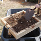 Push a sifter-full of soil and debris around with a shovel (or your hands) -the good compost will fall through the screen