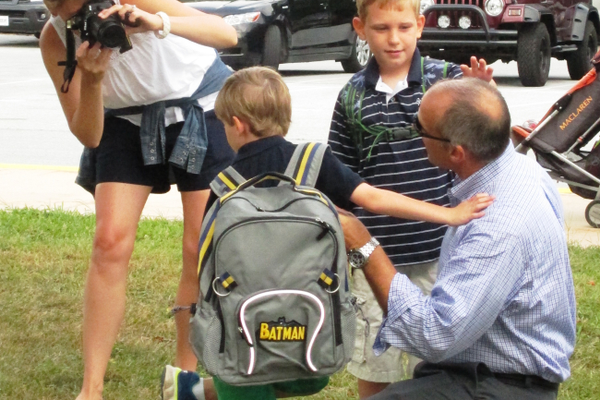 Families take time for a hug goodbye before school starts.
