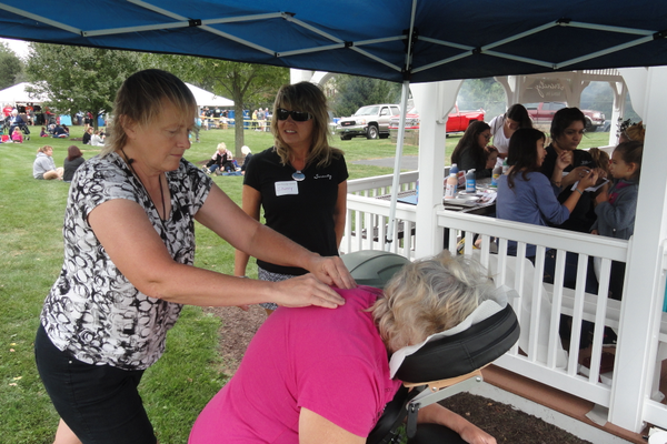 Lorie Struzik, a licensed massage therapist at Serenity Salon & Spa in West Grove, treats Joann Preston of Jennersville to a five-minute massage while salon owner Sherry Fagan looks on.