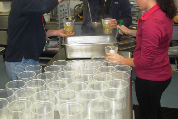 Volunteers ladle soup into containers at Hillendale.
