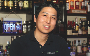 George Widjaja Little Leafs owner and sole bartender flanked by his artfully displayed liquor inventory