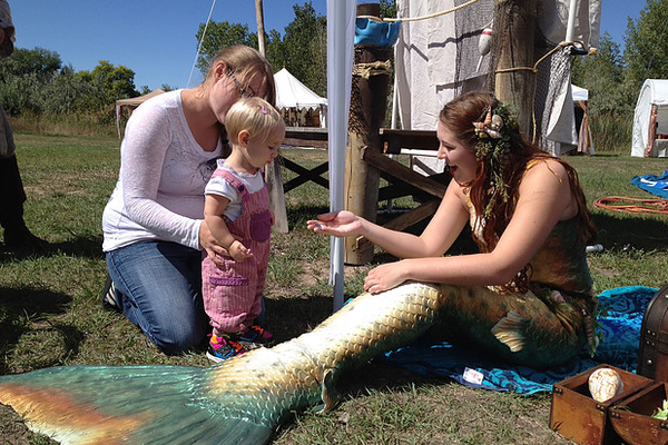 One of the Utah Mermaid actresses greets a child at an event. – Utah Mermaids