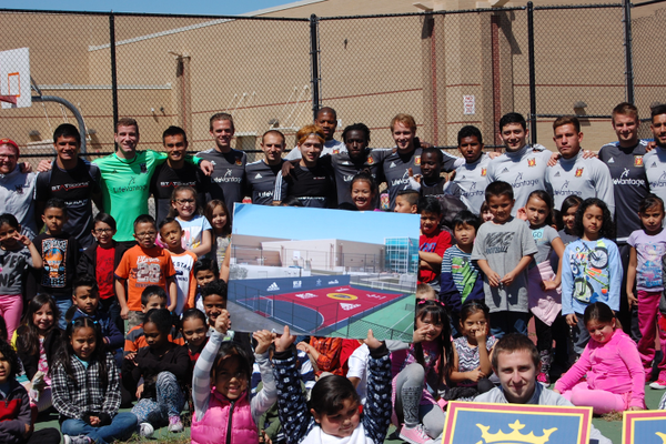 Students and players stop for photos as kids hold a picture of what the new court will look like. – Mary VanMinde