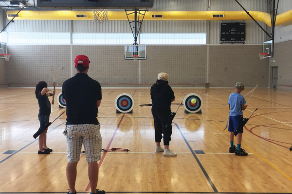 Instructor Bryce Rypien looks on as students fire their three arrows. The children are very keen on maintaining proper form, following rules of the range and practicing focus.