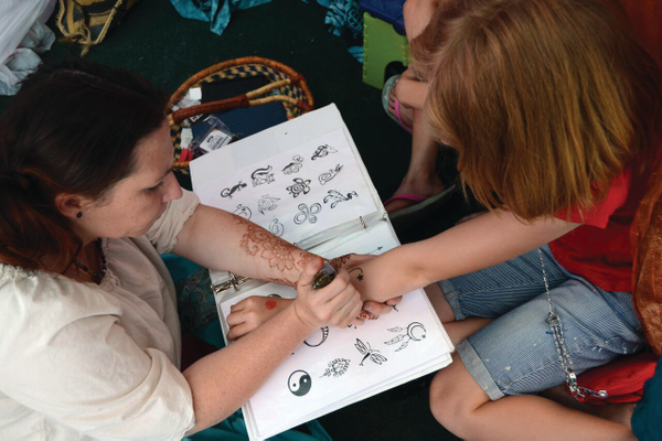 A henna artist draws a design on one of the patrons of the Holladay Farmers Market. —Kim Roach
