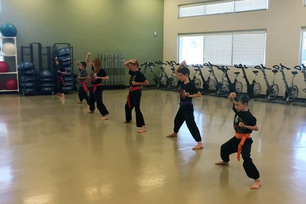 "After warming up, Shefu Mike Phan runs the students through a variety of striking drills. Here, students practice practice choi and li Uppercuts. Every kung fu student refers to Phan as ""Shefu,"" the Chinese word for ""teacher."""