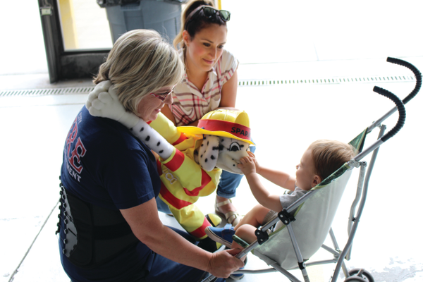 Fire Prevention Specialist Lenore Corey and her partner Sparky at the press event announcing the release of Parents Empowered videos featuring Sandy firefighters and the display of anti-underage drinking graphics on various Sandy firefighting vehicles at Sandy City Fire Station 31 on June 30, 2016. —Chris Larson