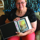 Elaine Wilcox displays a copy of one of her award-winning paintings. –Tori La Rue