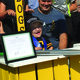 """9-year-old Nathan Glad shouts """"Hooray"""" after cutting the ceremonial ribbon at the grand opening of his hot dog stand. –Tori La Rue"""