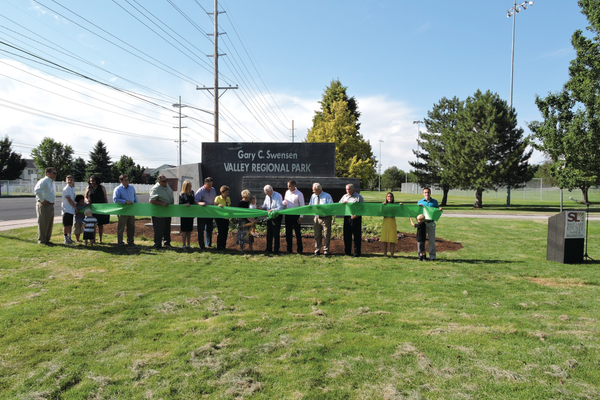 Members of the Swensen family hold the green ceremonial ribbon as Gary Swensen gets ready to cut it, symbolizing the official renaming of the park from Valley Regional Park to the Gary C. Swensen Valley Regional Park. In the past, Gary worked as Salt Lake County's land acquisitioner and superintendent and director of parks and recreation, so community members voted to name the county's park in Taylorsville after him. –Taylorsville City