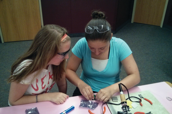 Cassandra Ivie (Right) helps another student solder a LCD screen. –Cassandra Ivie