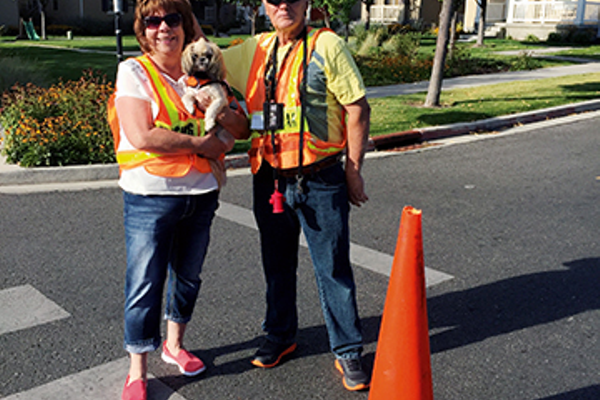 Daybreak Elementary husband-wife crossing guards Don and Vickie Hicks also include their therapy-trained dog, Buster, with their team. Their daughter crosses students nearby. (Julie Slama/My City Journals)