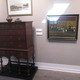 A 1729 walnut high chest stands next to Horace Pippin's The Milkman of Goshen.'