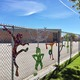 Tie-dye, dancing figures decorate the fence at Westbrook Elementary. (Tori La Rue/City Journals)