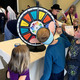 """Children spin a wheel to determine which character from """"Charlie and the Chocolate Factory"""" they are at the Viridian Event Center's Roald Dahl Day celebration on Oct. 7. (Tori La Rue/City Journals)"""