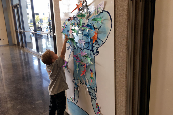 "Isaac Powell, 4, hangs a paper newt he colored on the paper cut-out of ""The Trunchbull,"" a character from the children's book ""Matilda."" Isaac and other community children celebrated Roald Dahl's books at the Viridian Event Center on Oct. 7. (Tori La Rue/City Journals)"