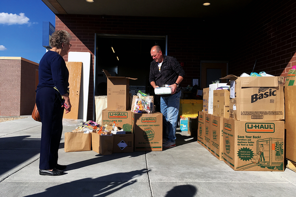 Ken Bullock of the Utah League of Cities and Towns speaks with Midvale Mayor JoAnn Seghini as they drop off 300 homeless kits at The Road Home in Midvale. (Travis Barton/City Journals)