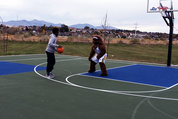 Cameron Peterson, Midvale youth of the year, plays one-on-one with the Jazz Bear after the Jazz court was opened with a ceremonial ribbon cutting on Oct. 27 at Bingham Junction Park. (Travis Barton/City Journals)