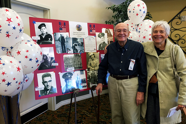 Standing by his World War II photographs, veteran Newel Ward, and his daughter Dianne Peck, were amongst those in the Carrington Court audience of Jordan Ridge's Veterans' Day program. (Julie Slama/City Journals)