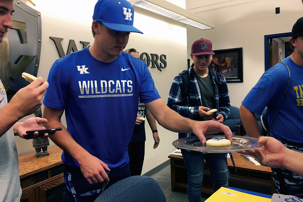 Crosby Bringhurst enjoys a cookie at the letter-signing celebration prepared for him in the main office at Taylorsville High School on Nov. 9. Bringhurst is a right-handed pitcher for the Warriors who signed with University of Kentucky. (Tori La Rue/City Journals)