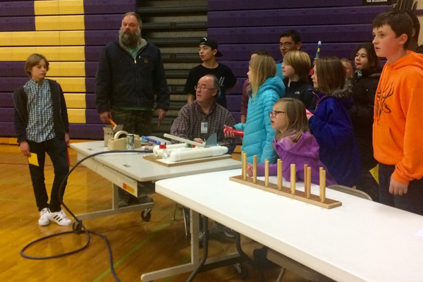 Phil Despain helps students launch paper rockets across the gym. (Rubina Halwani/City Journals)