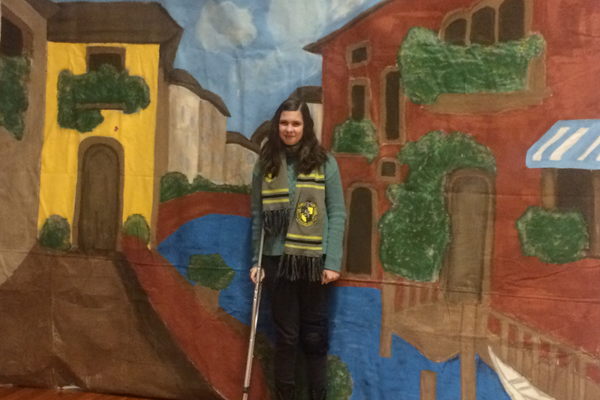 Midvale Middle School student Anna Day stands with the backdrop of Venice that she created with help from the stage crew class that will be used in a student production, which will be entered in an international student Shakespeare film festival. (Bethanne Lenhart/Midvale Middle School)
