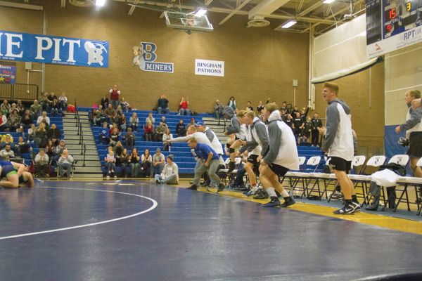 Bingham wrestlers and coaches cheer for someone on the mat. (Lauren Heap/Resident)