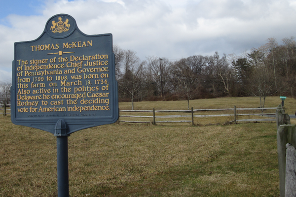 A marker for Thomas McKean near the home, visible behind the trees.