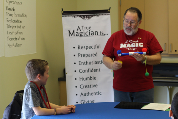 Jack Fenn, 9, watches as his magic instructor, Mont Dutson, performs a trick at the J.L. Sorenson Recreation Center in Herriman. (Tori La Rue/City Journals)