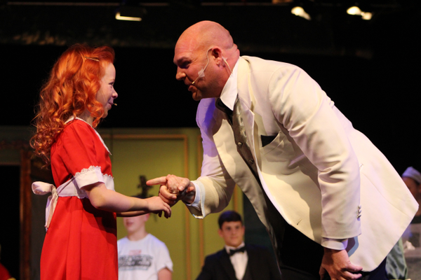 Elizabeth Birkner, playing the part of Annie, and Todd Young, playing the part of Oliver Warbucks, do a duet during Riverton Art's Council's latest musical production. (Tori La Rue/City Journals)