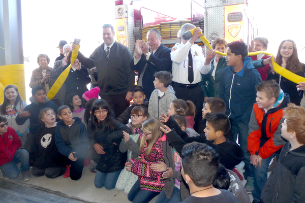 Instead of cutting a ribbon, officials opened the new station by uncoupling a fire hose. (Carl Fauver/City Journals)