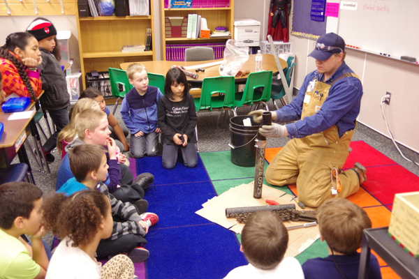 Commercial pipefitter and plumber foreman Daniel Berry shows East Midvale Elementary students a pipe after he cut it during Career Day. (Julie Slama/City Journals)