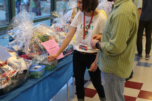 People drop their tickets into boxes for the theme basket raffle. (Travis Barton/City Journals)