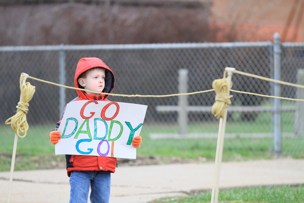 A young spectator rooting on his favorite runner in the Family 5K Run and Fun Walk
